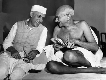 Mahatma Gandhi and Nehru sit together black and white smile and laugh